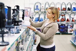 Woman picking up a blender in a store