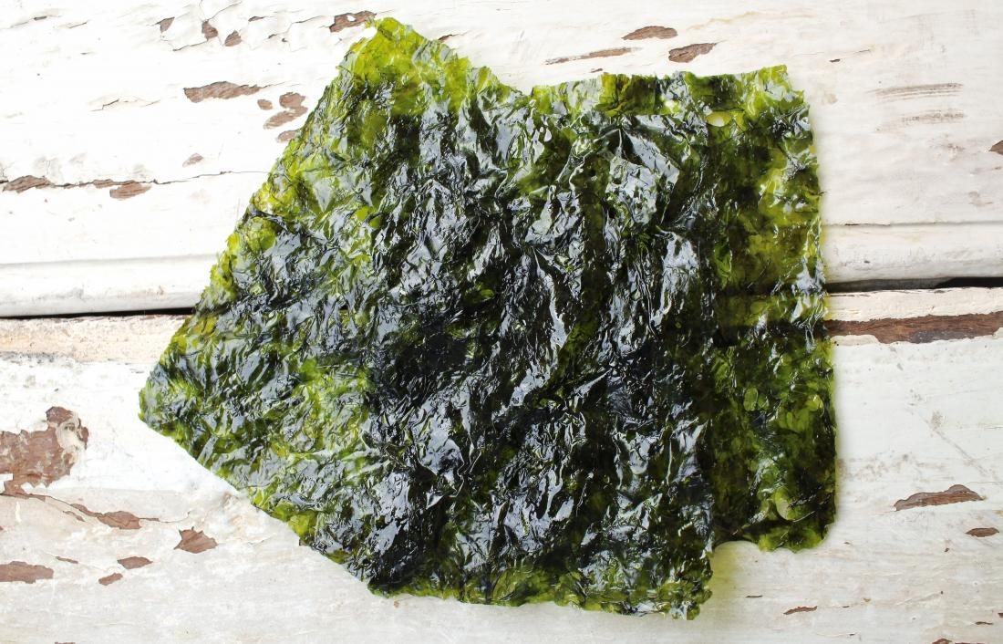 Nori seaweed sheets on wooden surface