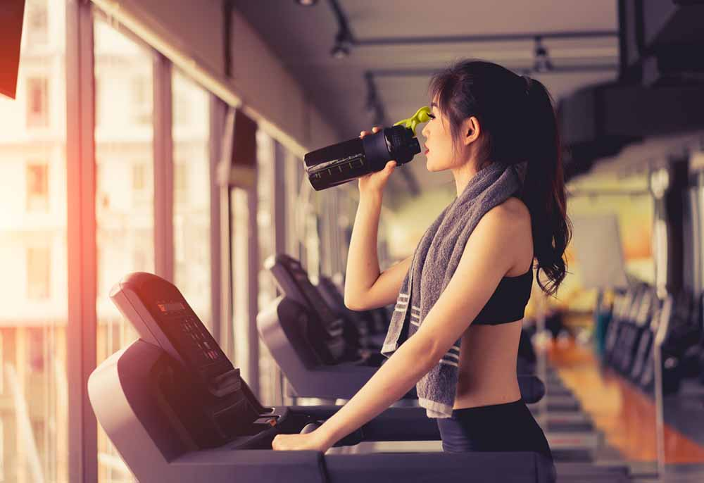 Low-calorie-weight-loss-shakes-woman-drinking-shake-on-treadmill