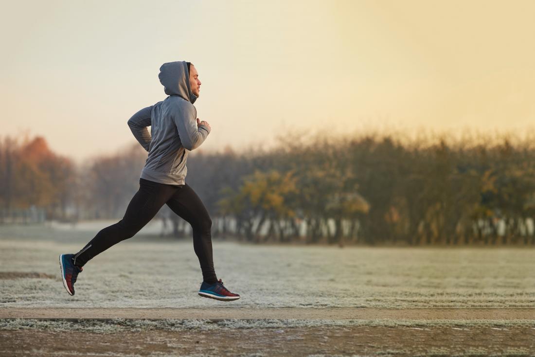 man jogging or running through park in winter