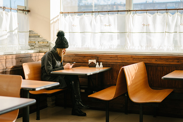 woman sitting alone diner cloaked
