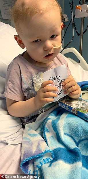 The now-three-year-old is pictured in hospital, where she endured chemo, radiotherapy and 13 brain surgeries