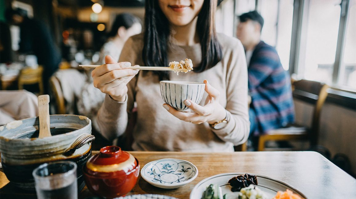 Japanese woman eating rice at restaurant