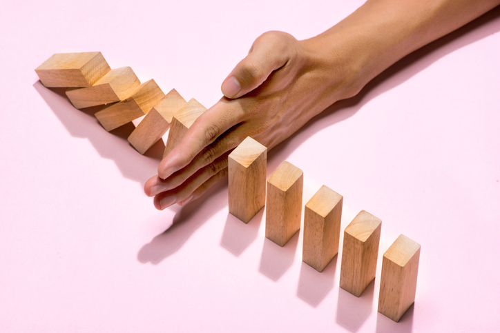 anxiety and coping strategies concept; hand stops blocks from falling in a chain reaction