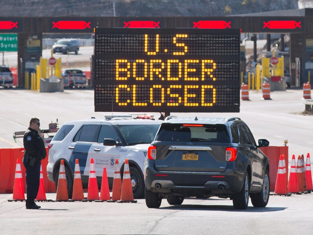 US Customs officers speak with occupants of a vehicle at the US/Canada border in Lansdowne, Ont., on March 2020.